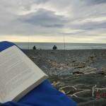Lesen am Strand hinter Anglern am Meer