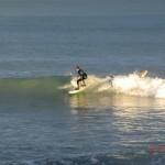 Surfer auf einer goldenen Abendwelle