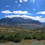 wieder Steppe und Bergketten unter blauem Himmel