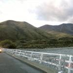 Joy auf der Brücke unterhalb der Berge