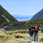 über Holzstege durch alpine Steppen, Lake Pukaki blitzt in der Ferne zwischen den Bergen durch