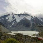 prächtiger Berg mit Schnee, See und Raupenwolke