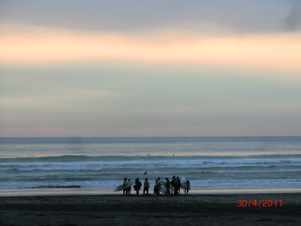 Surfer im Abendrot am Piha Beach